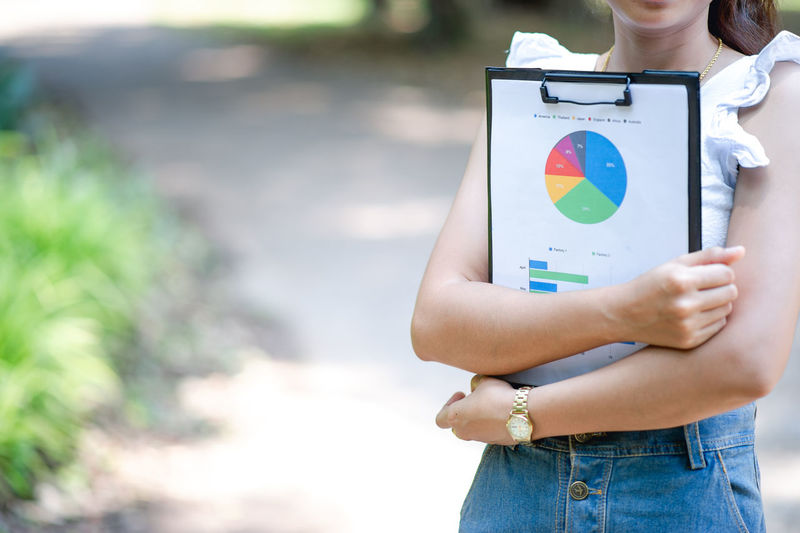Midsection of businesswoman holding clipboard with data