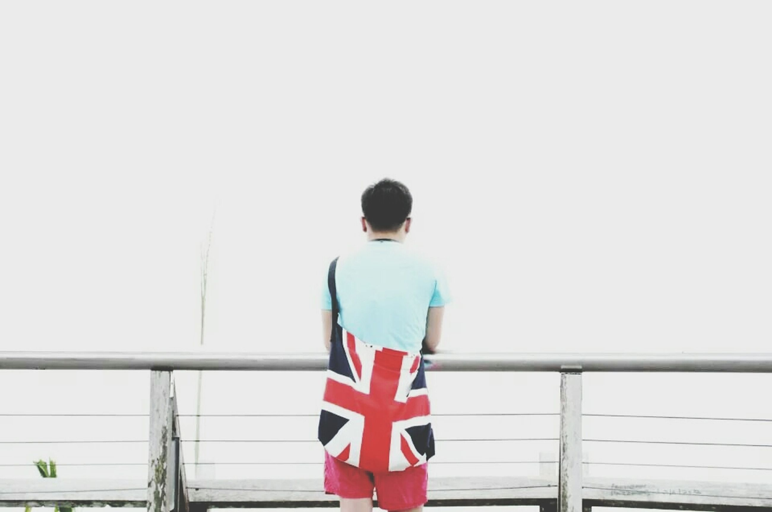 rear view, standing, lifestyles, casual clothing, copy space, leisure activity, clear sky, railing, red, full length, striped, three quarter length, day, person, side view, white color, flag, waist up