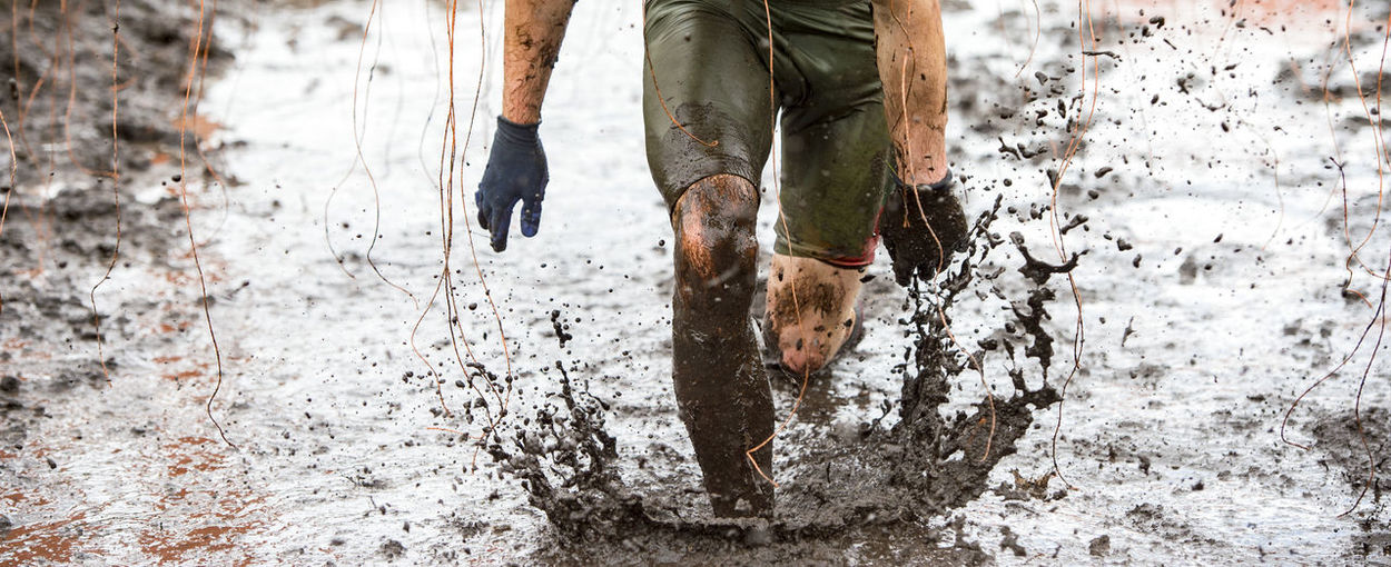 Low section of man running in mud
