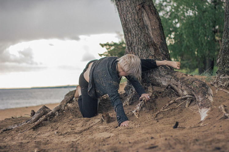 Rear view of woman relaxing on tree trunk