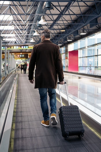Rear view of man walking in airport