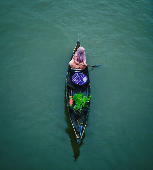 High Angle View Of Woman Rowing Boat On Lake