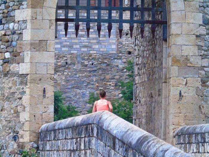 Rear view of woman standing at castle entrance