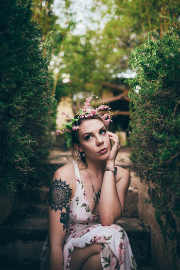 Beautiful young woman with flower on tree