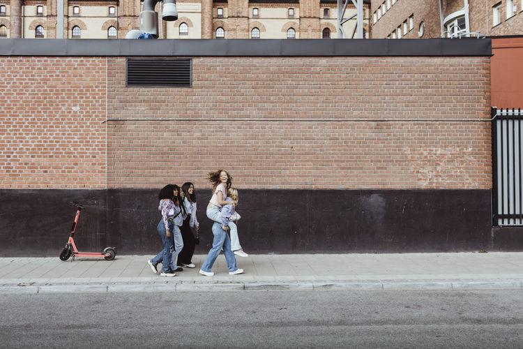 People walking on footpath against building in city