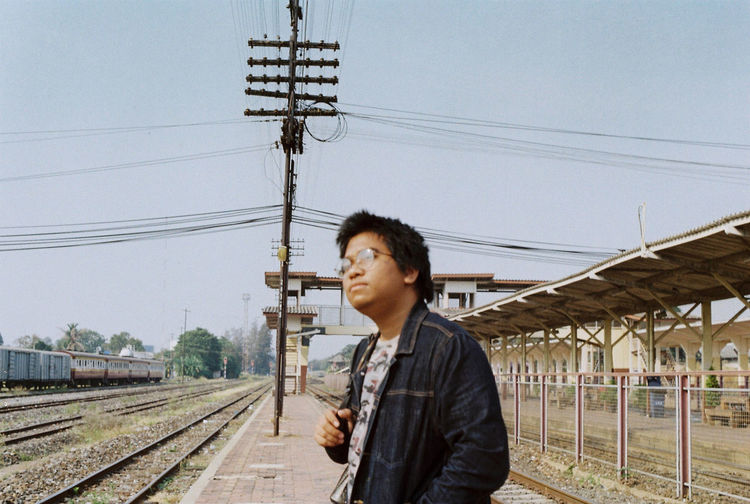 Young man using mobile phone by railroad tracks against sky