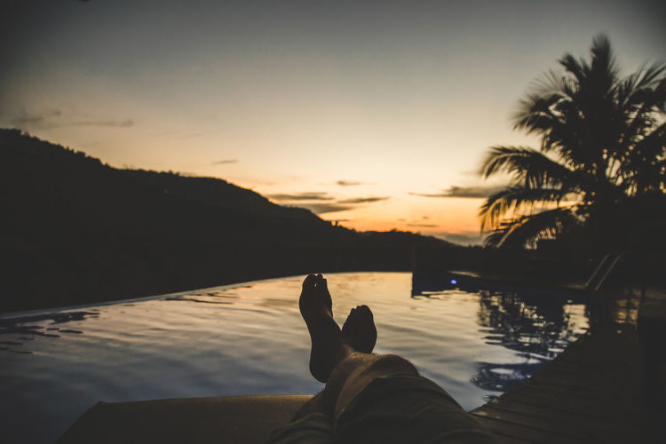 Low section of man relaxing by infinity pool during sunset