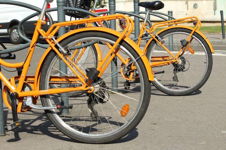 EyEmNewHere Orange Color Bicycle Rack City Spoke Bicycle Stationary Pedal Tire Land Vehicle Wheel Street Chain