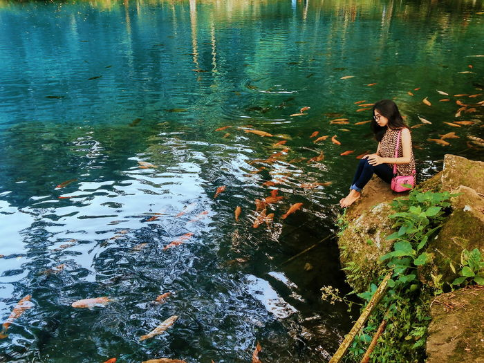 High angle view of girl sitting by lake