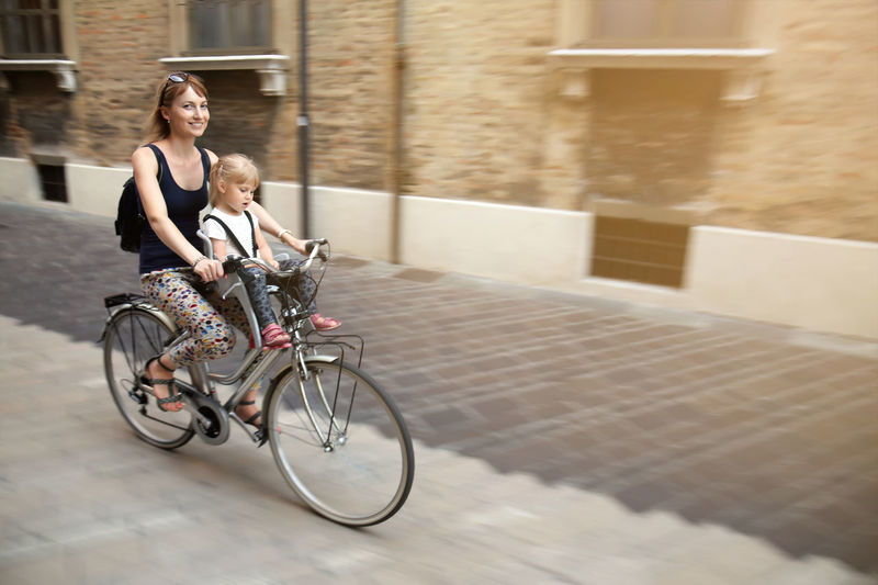 Woman cycling with daughter on footpath