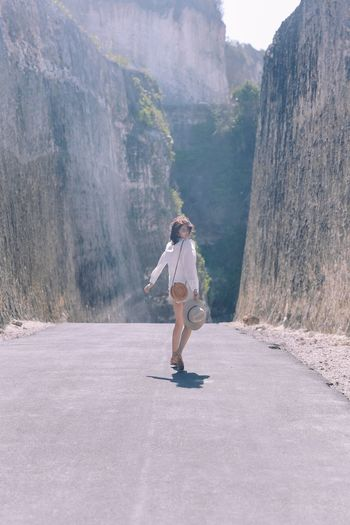 Full length side view of woman walking on mountain road