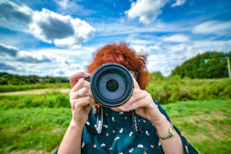 Close-up of woman photographing against sky