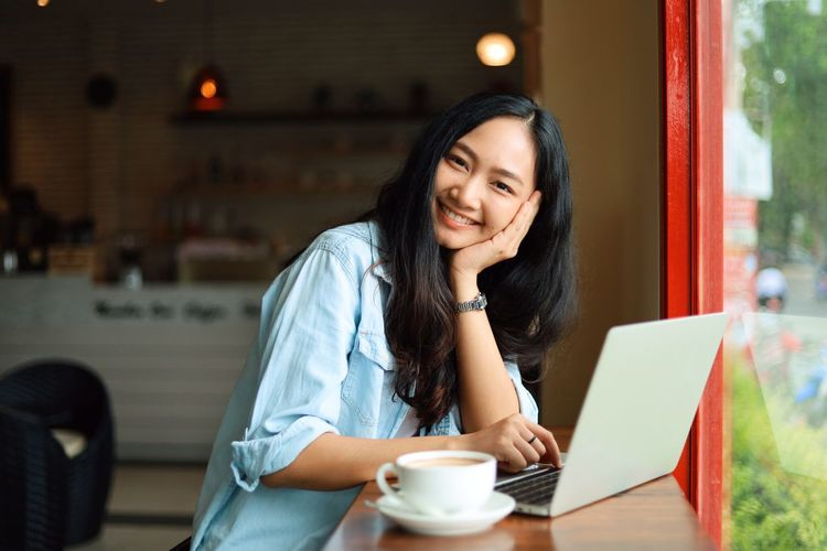 Laptop Computer Wireless Technology Communication Technology One Person Sitting Smiling Using Laptop Young Adult Cafe Cup Mug Connection Adult Coffee Cup Table Coffee Happiness Food And Drink Hair Hairstyle Beautiful Woman