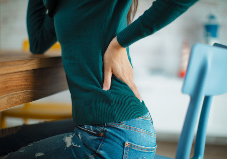 Young woman with back pain Human Body Part Body Part Lifestyles Sitting Woman Pain Backache Ache Lumbar Infiammation Stretching Physical Activity Back Hand Hand On Hip Teal Yoga Stress Stressed Jeans Modern Interior