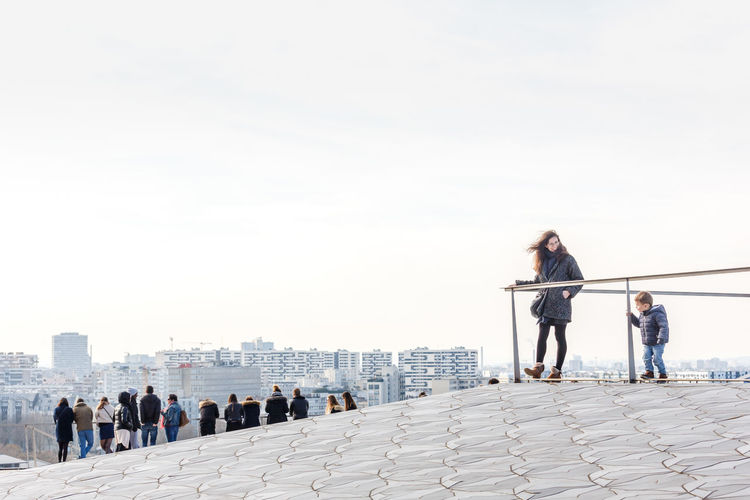 Friends standing on railing in city against clear sky