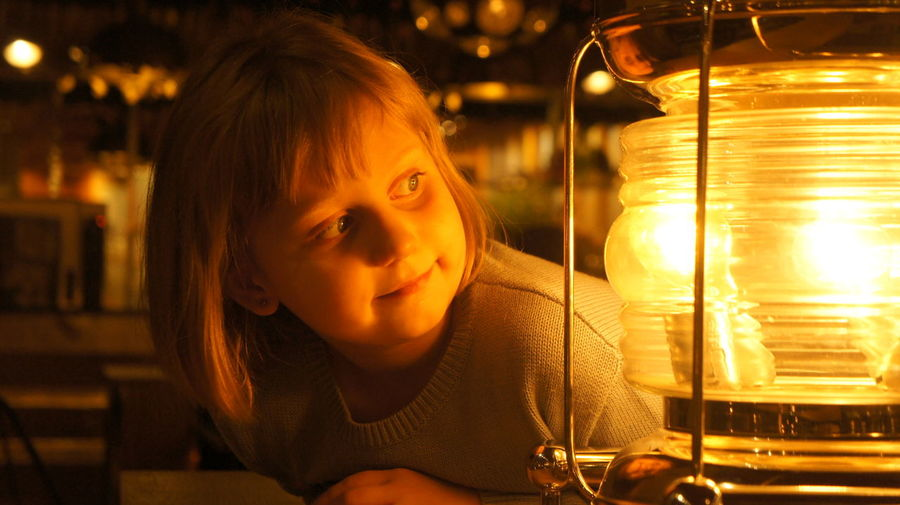 Close-up portrait of girl looking at illuminated lamp