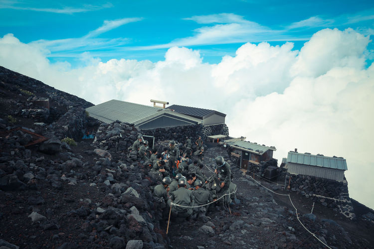 High angle view of army soldiers on mountain of against sky