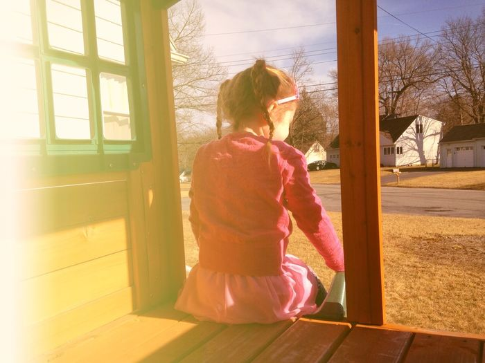 Rear view of girl sitting at porch on sunny day
