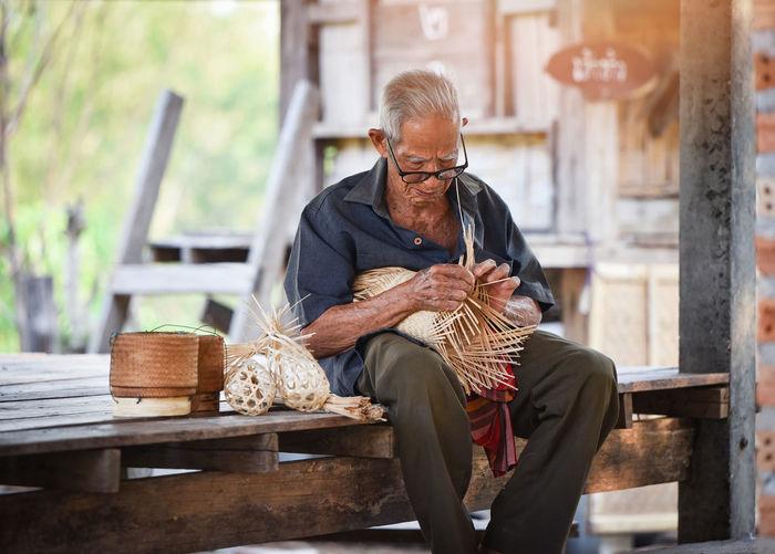 Man making art product while sitting on wood
