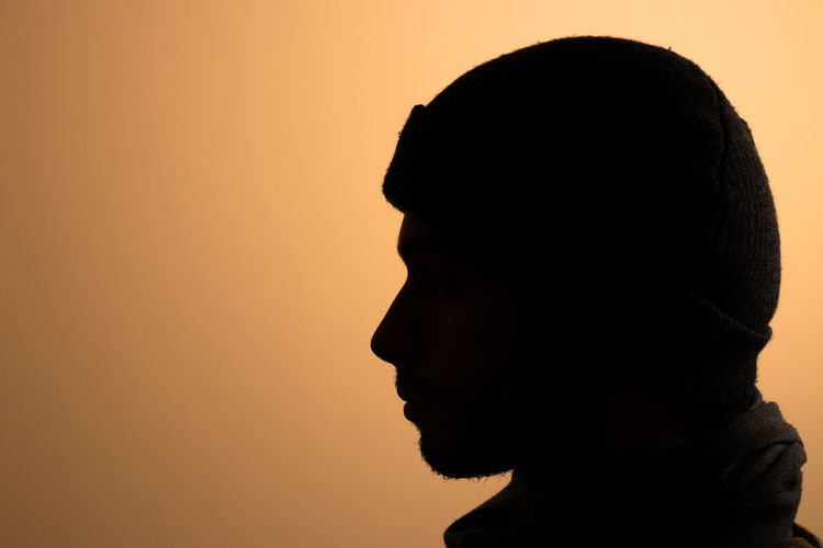 Close-up portrait of silhouette man against orange sky