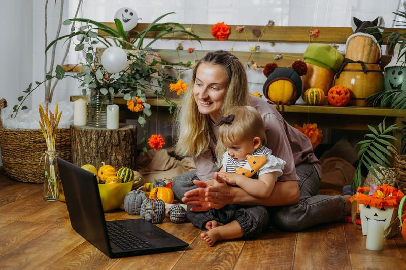 Mother with daughter clapping while sitting in front of laptop on floor at home