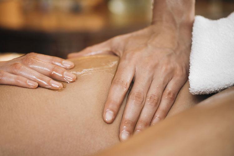 Alternative medicine. ayurvedic body massage close-up pressing on thighs