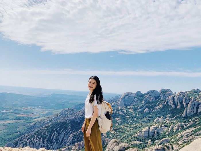 Portrait of young woman standing against mountains and sky