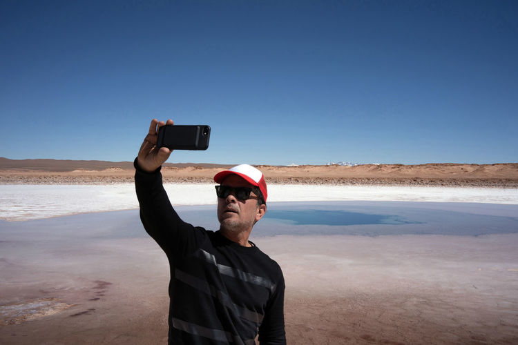 Man taking a selfie with the background of the andes mountain range