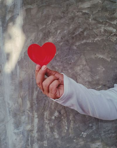 Cropped image of hand holding heart shape against blurred background