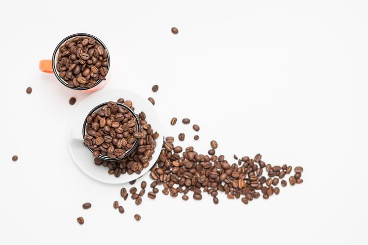 Top View of Coffee beans in a White Coffee cups on White Background Food And Drink Food Roasted Coffee Bean Coffee - Drink Freshness Coffee Indoors  Studio Shot White Background Still Life Brown Large Group Of Objects High Angle View No People Coffee Bean Drink Directly Above Table Close-up Refreshment Temptation