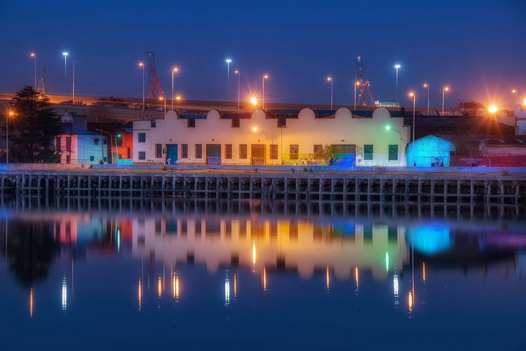 Illuminated industrial buildings with reflection on lake at night