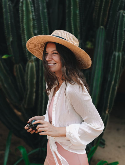 Smiling woman wearing hat while walking by plants