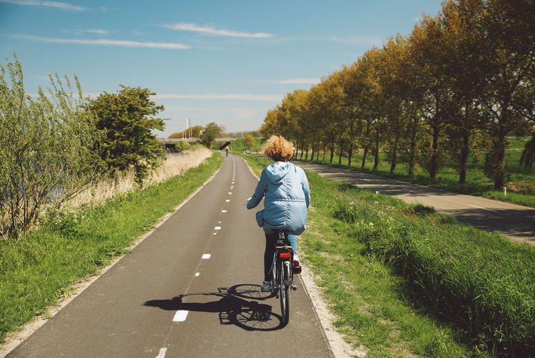 Rear View Of Woman Riding Bicycle On Road Against Sky During Sunny Day
