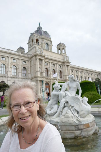 Smiling Mature Woman Standing Against Statues At Hofburg Palace