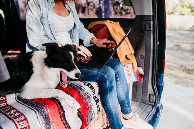 Midsection of woman using laptop while sitting with dog in camper trailer