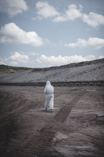 Rear View Of Worker In Protective Clothing At Mining Industry Against Sky
