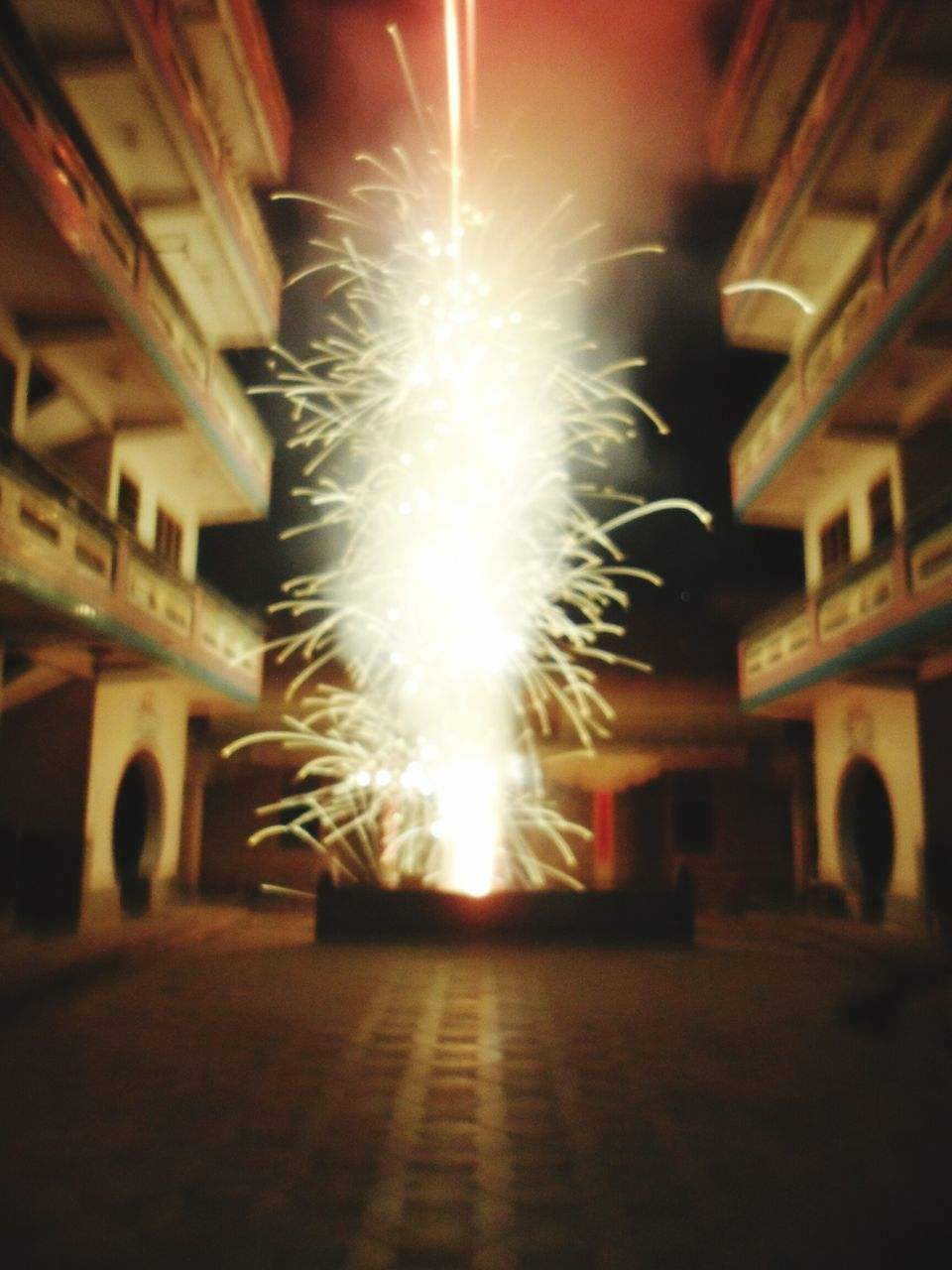 night, illuminated, glowing, celebration, built structure, architecture, firework - man made object, building exterior, long exposure, low angle view, no people, firework display, motion, outdoors, city, sky