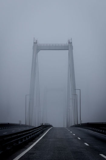 Bridge over road against sky during foggy weather