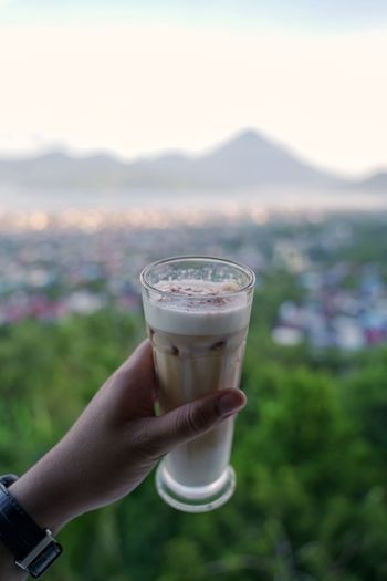 Midsection of person holding drink against mountain