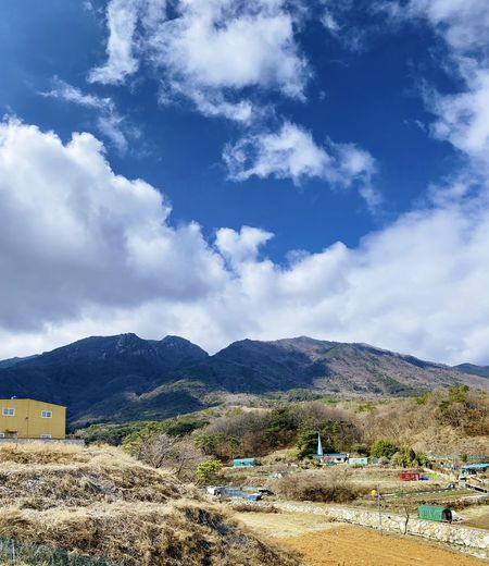 Scenic view of landscape and houses against sky