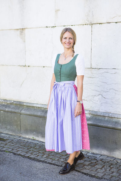 A young German female poses in front of the camera at the Octoberfest in Munich, Gemany Adult Adults Only Beautiful Woman Blond Blond Hair Blue Eyes Confidence  Day Dirndl Front View Full Length Happiness Lifestyles Looking At Camera Octoberfest One Person Outdoors People Pigtails  Portrait Real People Smiling Standing Young Adult Young Women