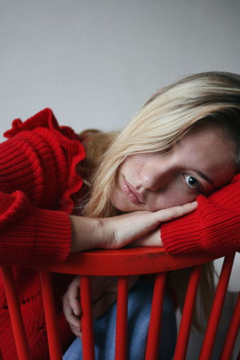 Close-Up Portrait Of Sad Young Woman Leaning On Red Chair