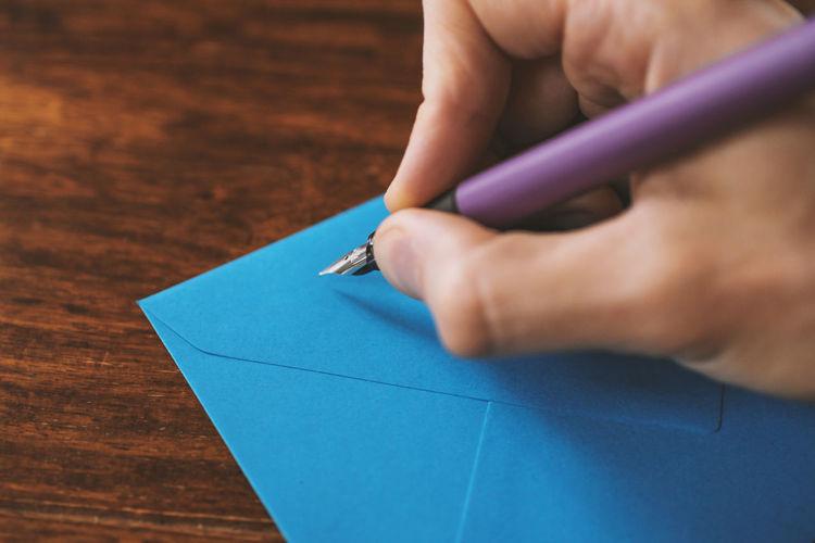 Cropped image of man writing on blue envelope