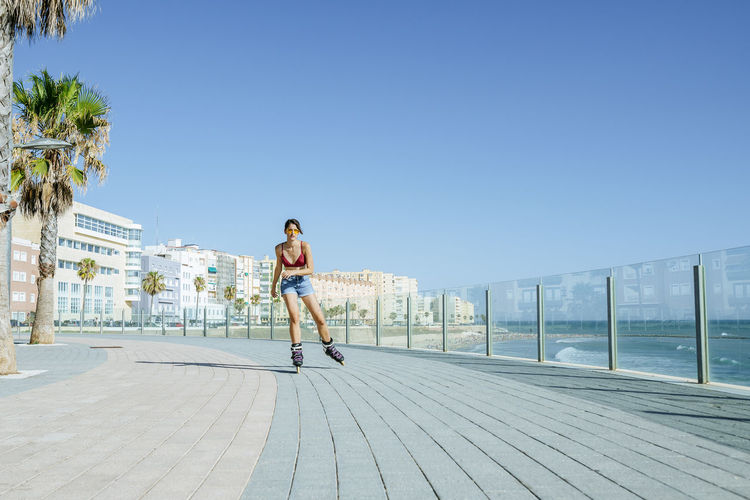 Rear view of woman on footpath against clear sky
