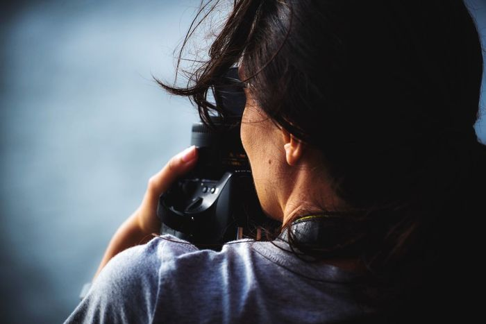 Technology One Person Holding Headshot Photography Themes Camera - Photographic Equipment Portrait Adult Activity Photographing Leisure Activity Close-up Real People Women Indoors  Wireless Technology Hair Lifestyles Communication Photographer