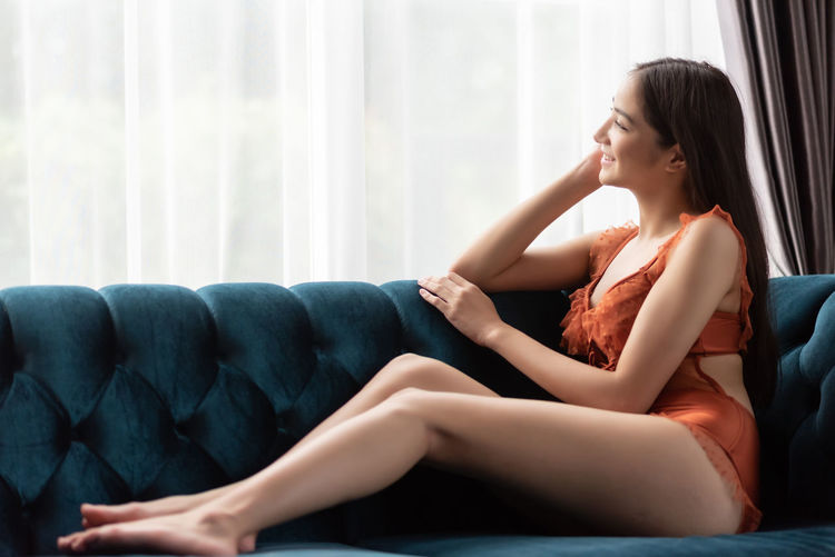 Side view of young woman looking away sitting at home