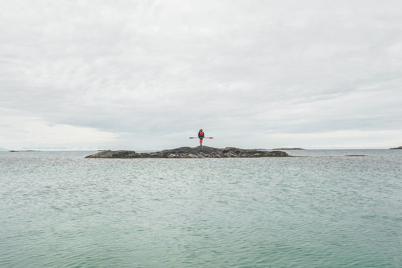 Scenic view of kayaker on rock on sea