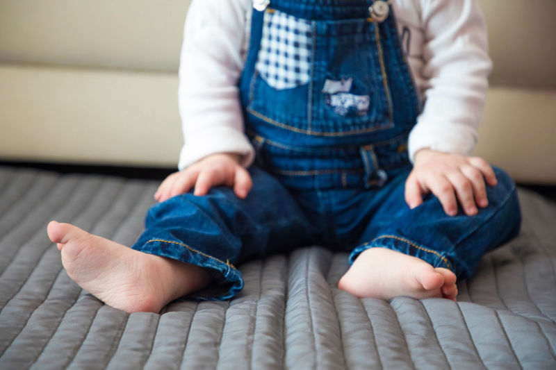 Jeans Baby Baby Boy Babyhood barefoot Bed Bonding Boys Casual Clothing Childhood Cute Day Father Front View Full Length Home Interior Human Body Part Human Hand Human Leg Indoors  Jeans Leisure Activity Lifestyles Low Section One Person Real People Sitting Toddler