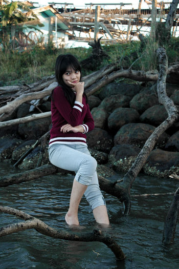 Smiling young girl looking away while sitting on fallen tree over river