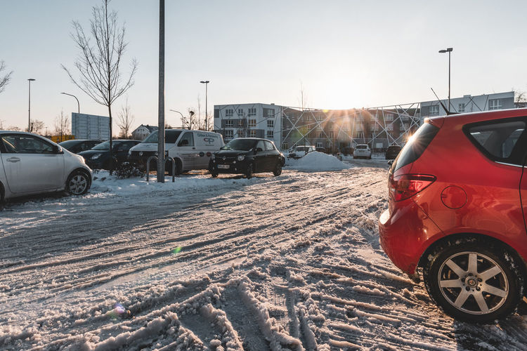 Cars on street against snowcapped mountains in winter